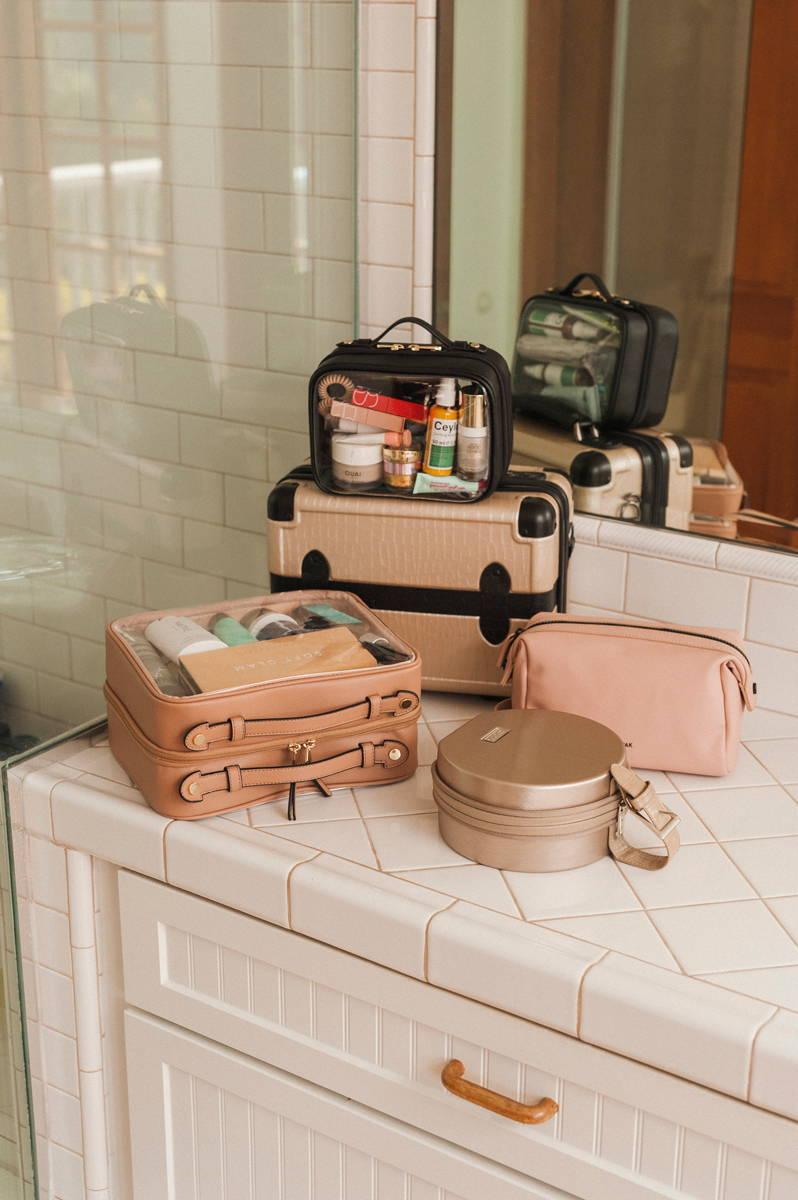 CALPAK Clear Cosmetics Case in Caramel, Baye Mini in Gold, Hue Toiletry Bag in Pink Sand, Vanity Case in Trnk Nude, and Mini Clear Cosmetics Case in Black
