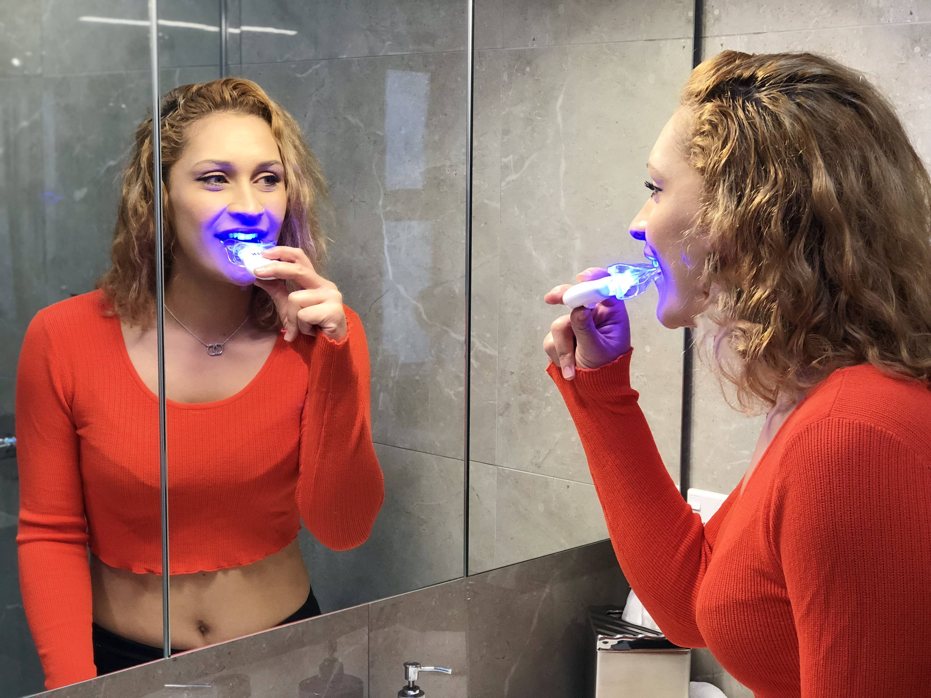 girl in the mirror with teeth whitening led light