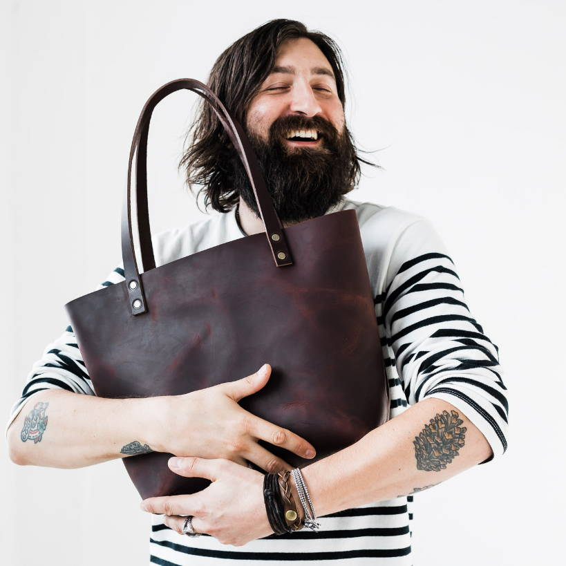 bearded man hugging handmade leather tote bag by portland leather goods