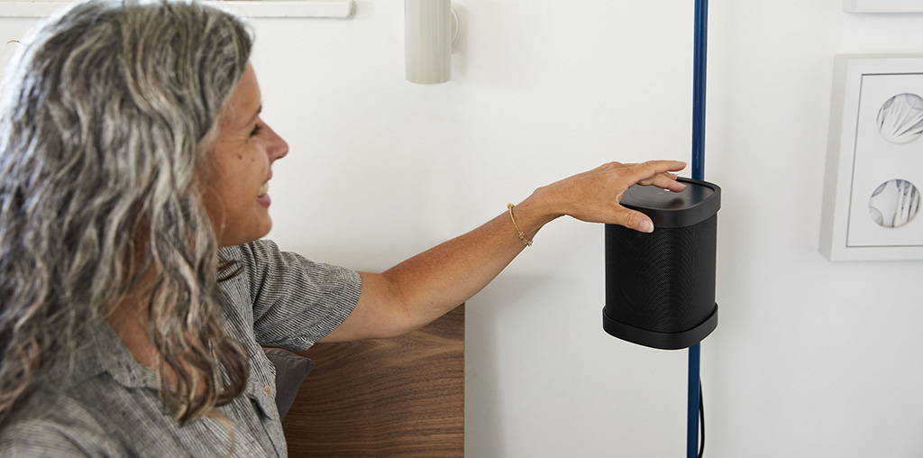 A women enjoys the easy top touch controls of Sonos One.