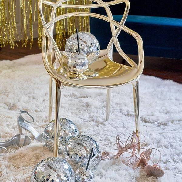 A glitzy photo of a gold chair on a fur rug with disco balls, disco ball cups, and high heels strewn around it with a backdrop of gold hanging foil