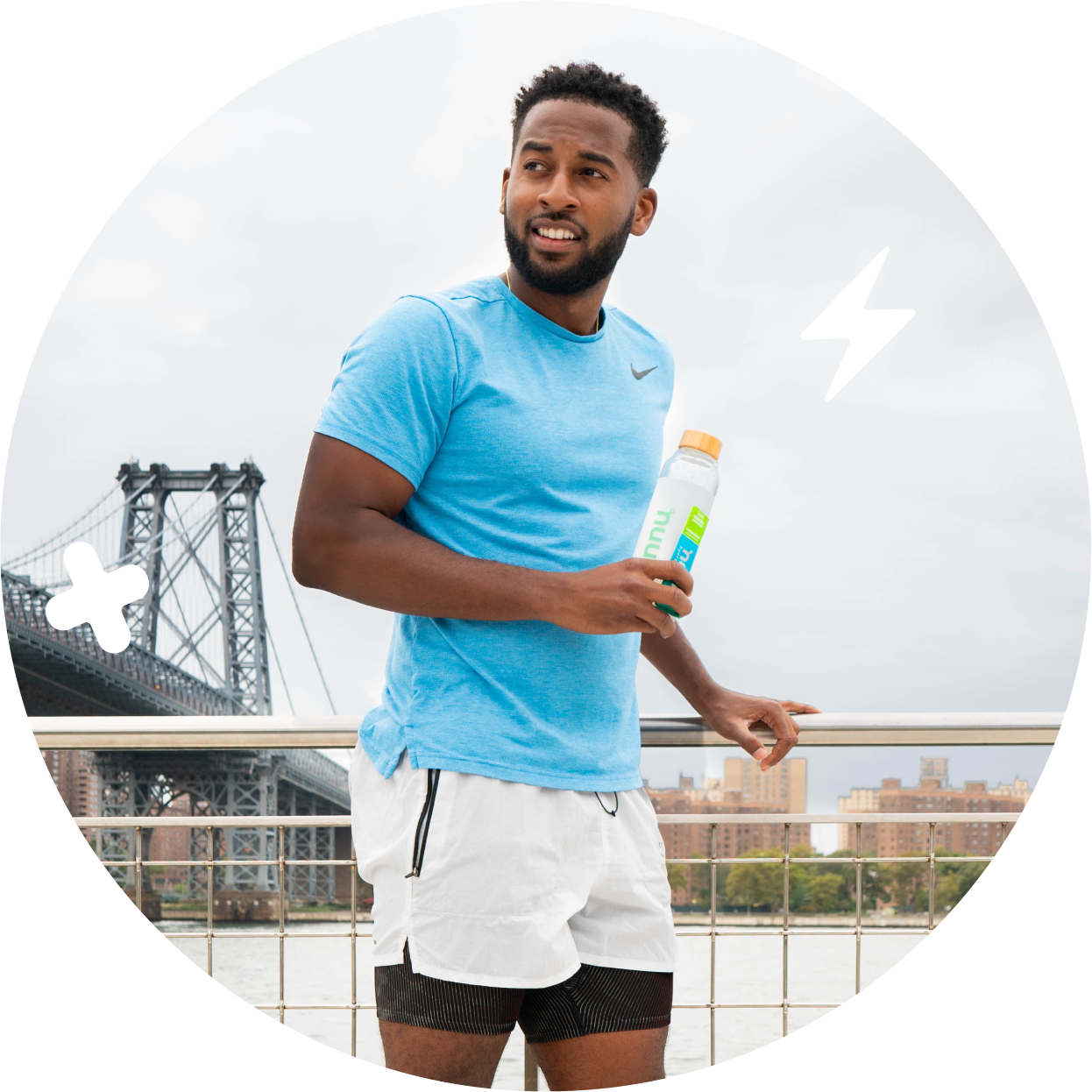 Man standing by a bridge holding a water bottle and Nuun Instant