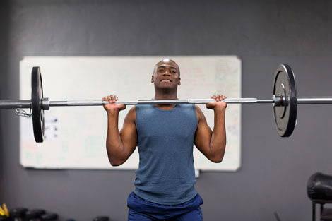 Mann macht Übung aus einem Muskelaufbau-Trainingsplan