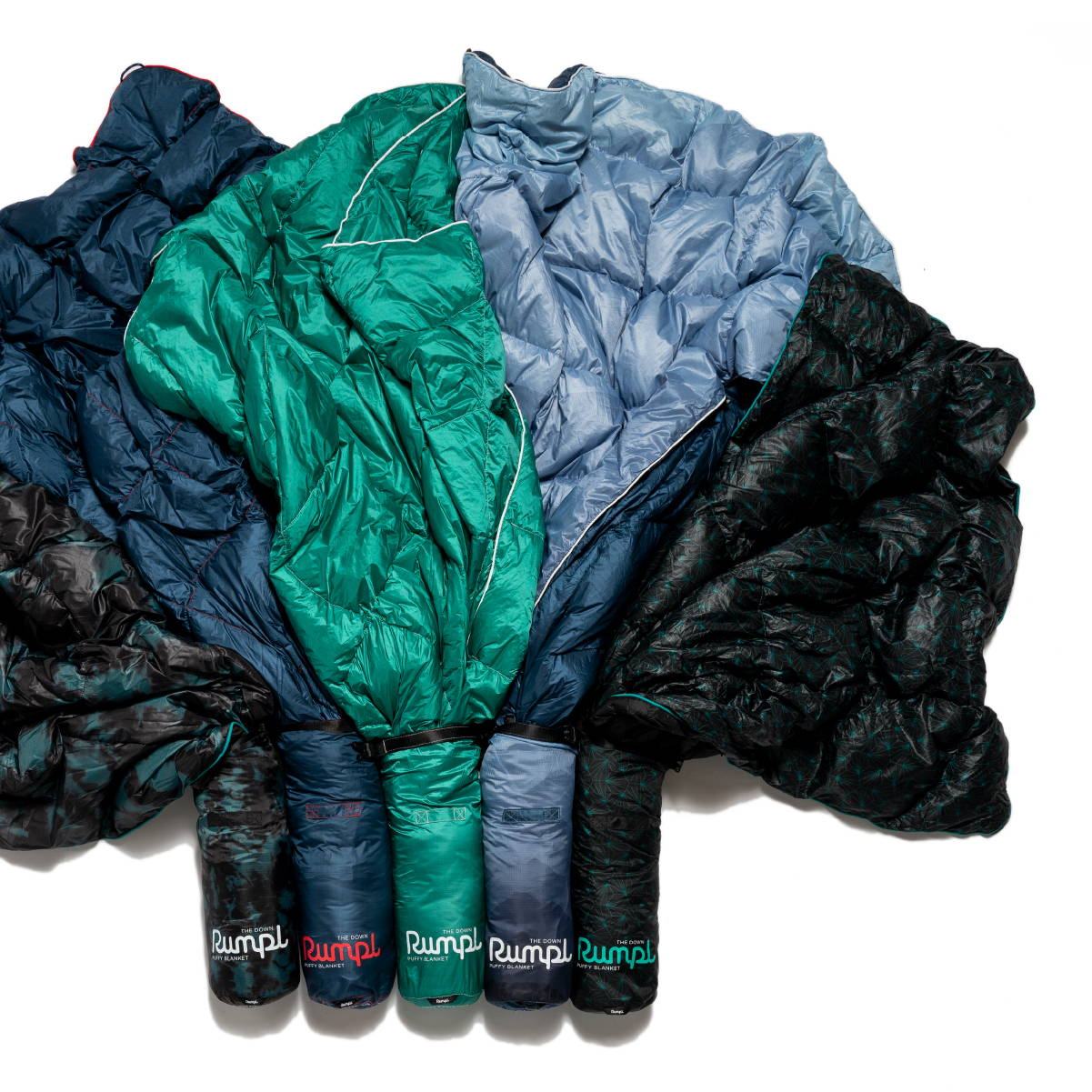 Blue Green Purple and Black sleeping bag Rumpl blankets laying in a pile