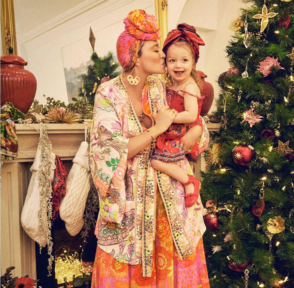 CAMILLA holding Luna next to Christmas Tree