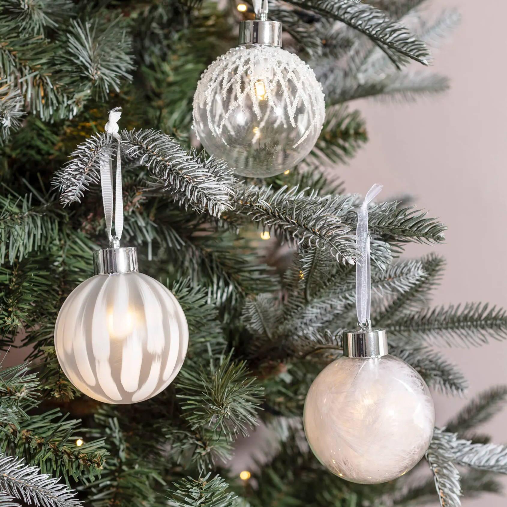 Drei weiße Weihnachtsbaumkugeln mit LED-Licht.