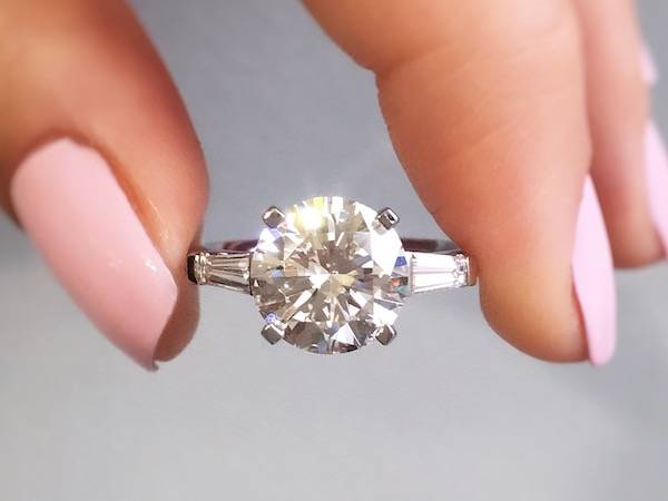 person holding a round diamond rinng