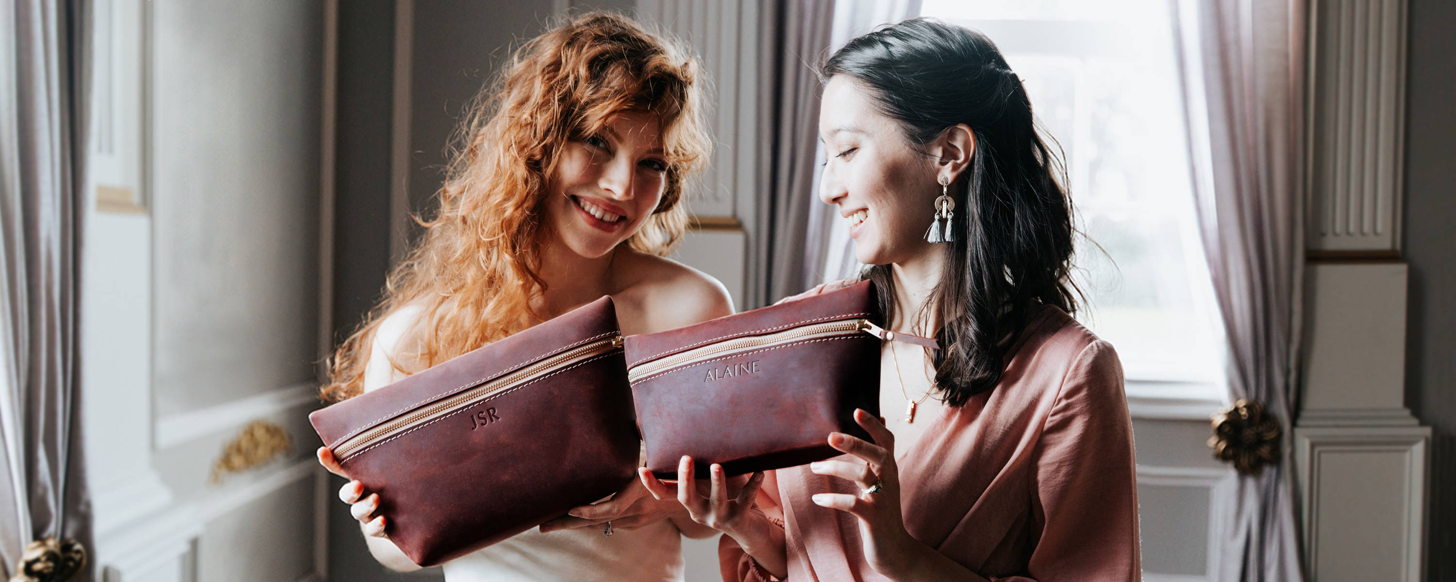 bridesmaid and bride holding merlot handmade leather makeup bags