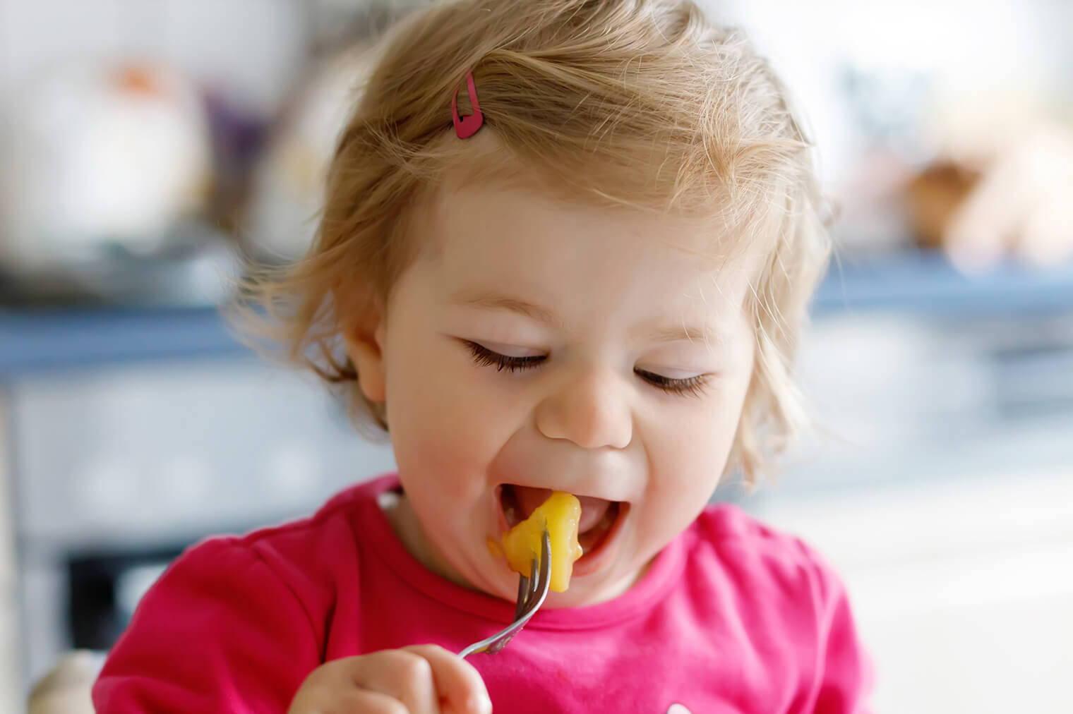 vitabiotics child eating solid food with fork