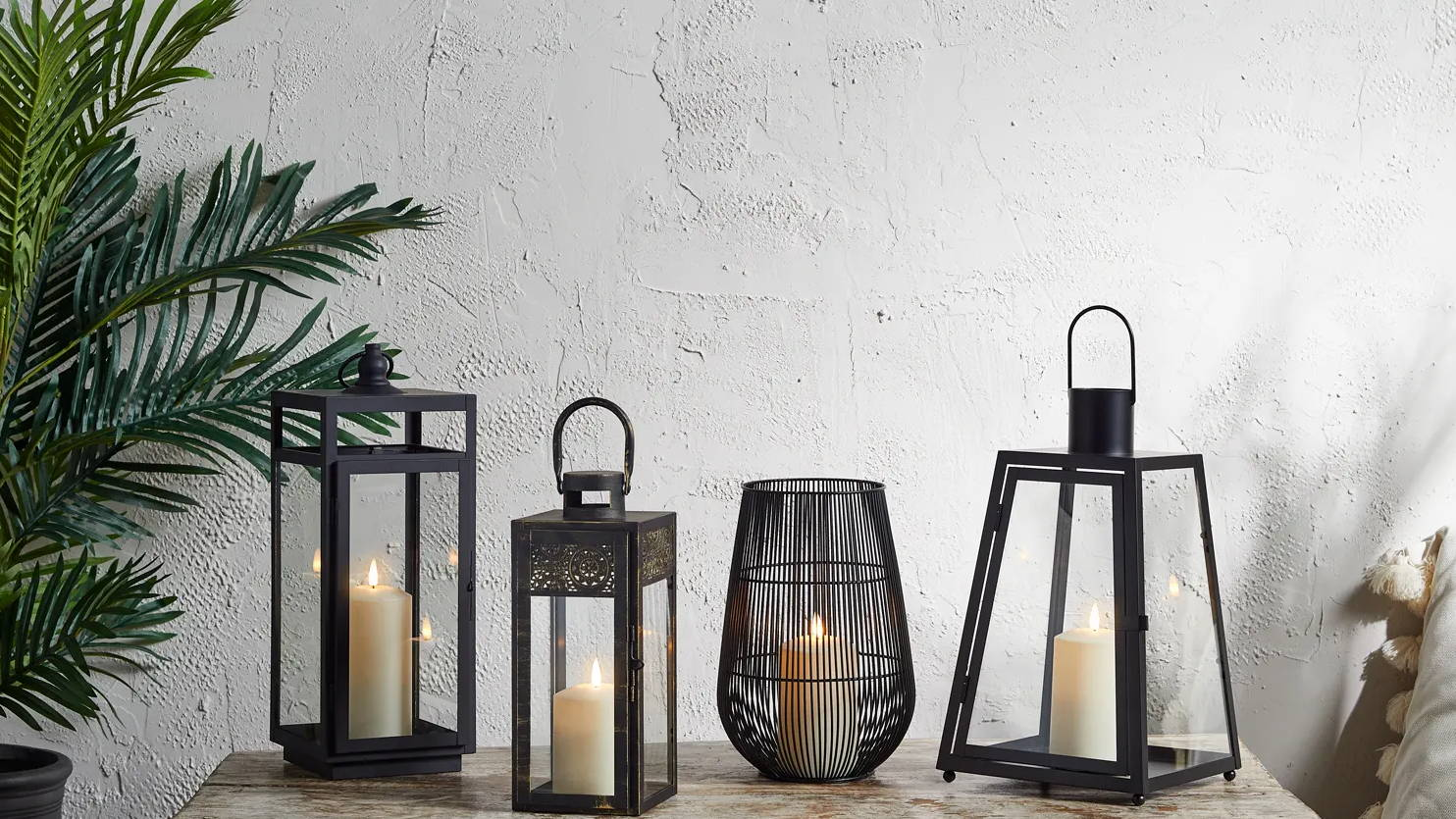 Assortment of black metal lanterns with TruGlow candles sat on table