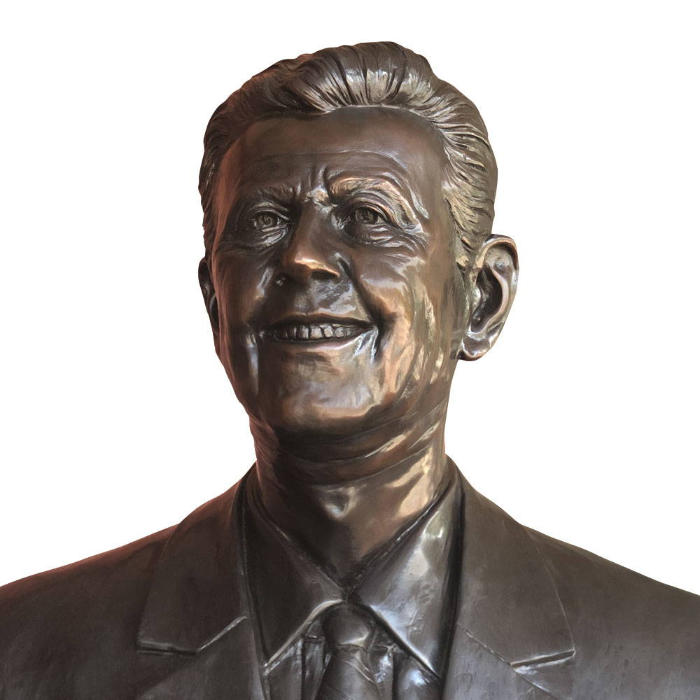 A bronze mold of a man smiling and wearing a suit