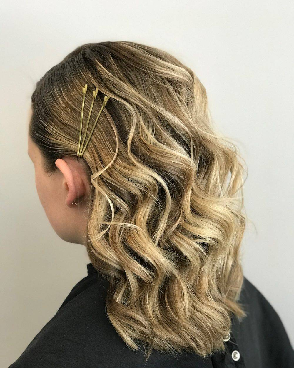 Girl with curly hair and gold bobby pins