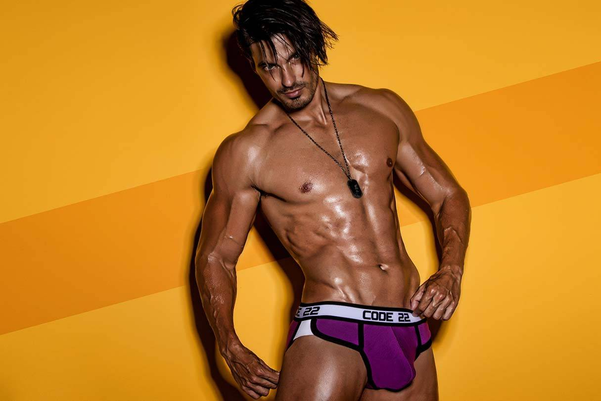 Code 22 Mens Underwear, Sportswear and Swimwear | It's About The Man | Male Model wearing Code 22 Underwear on Yellow Background, Man in Briefs, Mens Purple Briefs