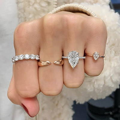 Hand with Pear diamond ring and multiple fashion rings