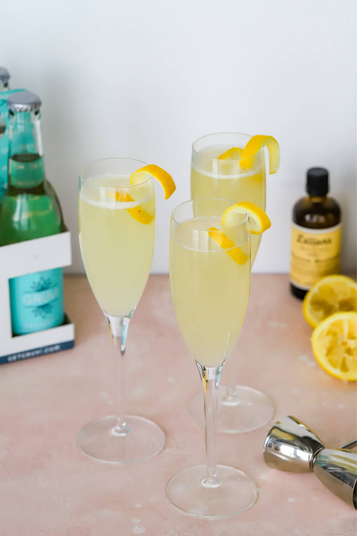 Three champagne flutes filled with non alcoholic french 75 and each topped with a lemon twist.