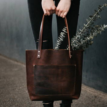 hands holding handmade grizzly leather tote bag with green plants sticking out