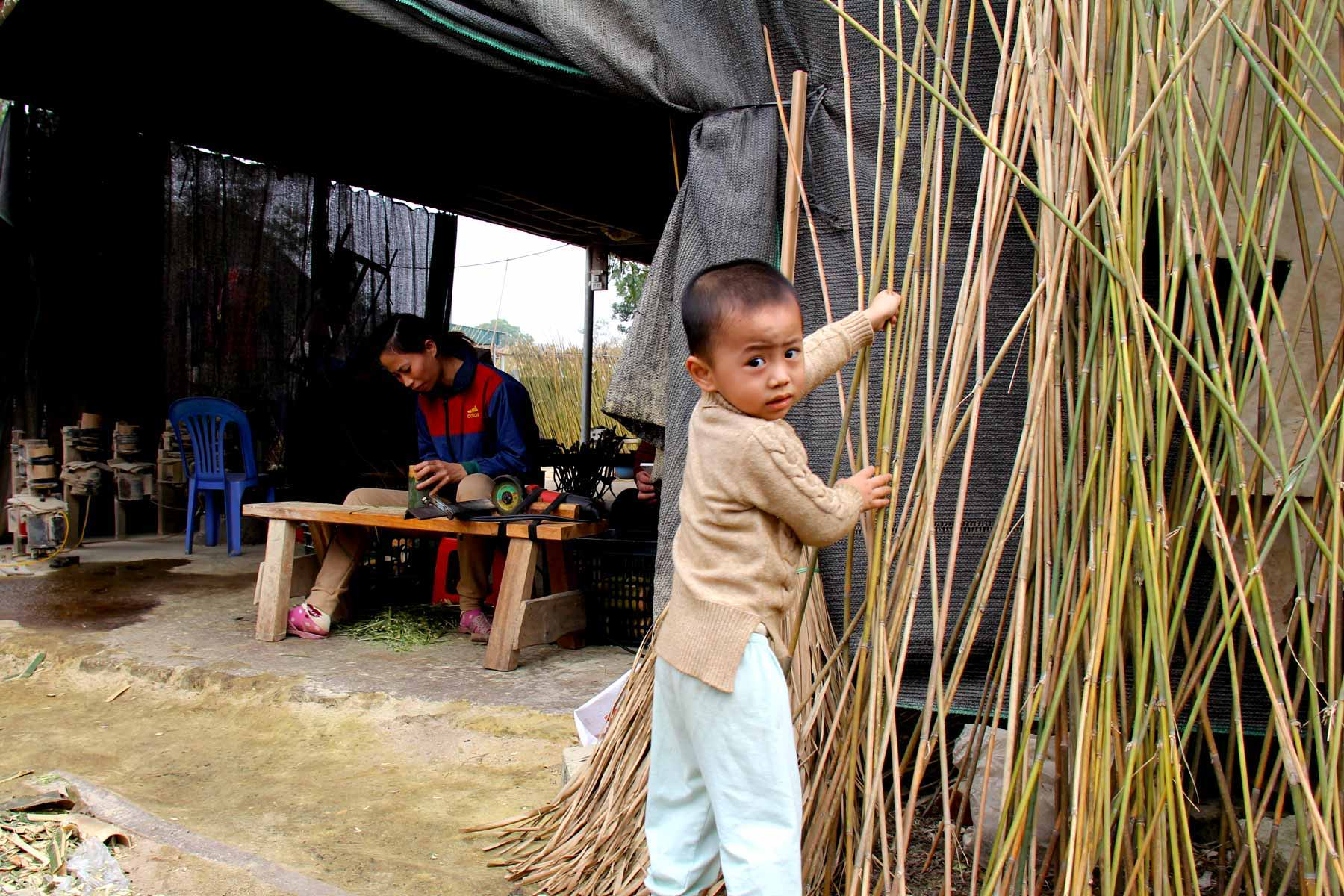 Child playing with bamboo stalks in Vietnam