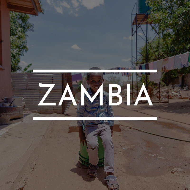 """""""ZAMBIA"""" Is written on top of an image of boy sitting on a bucket outside his orphanage."""
