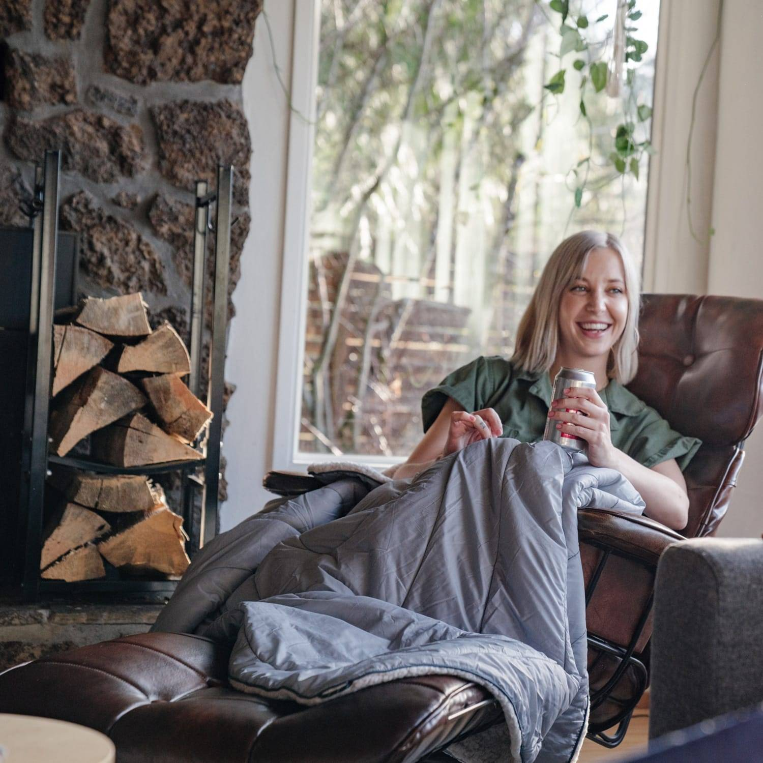 Woman under a throw blanket drinking a beer on a chair