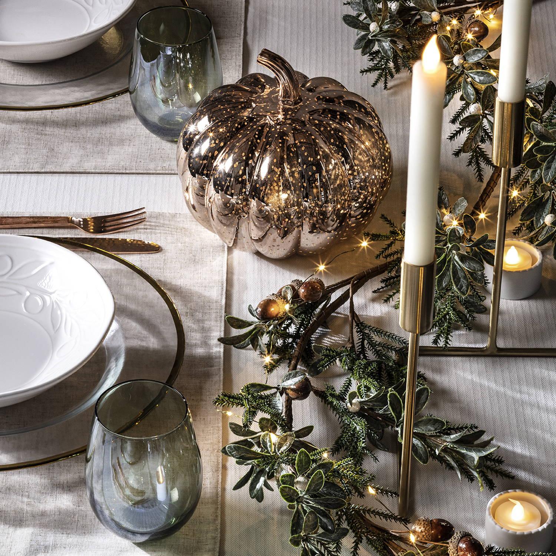 Rotgoldener Kürbis und Teelichter auf gedecktem Tisch.