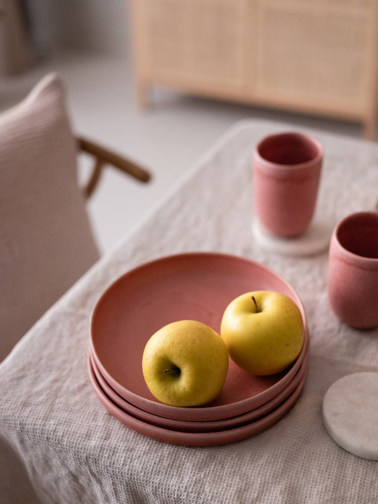 Pink Malhou stoneware crockery with linen tablecloth and apples
