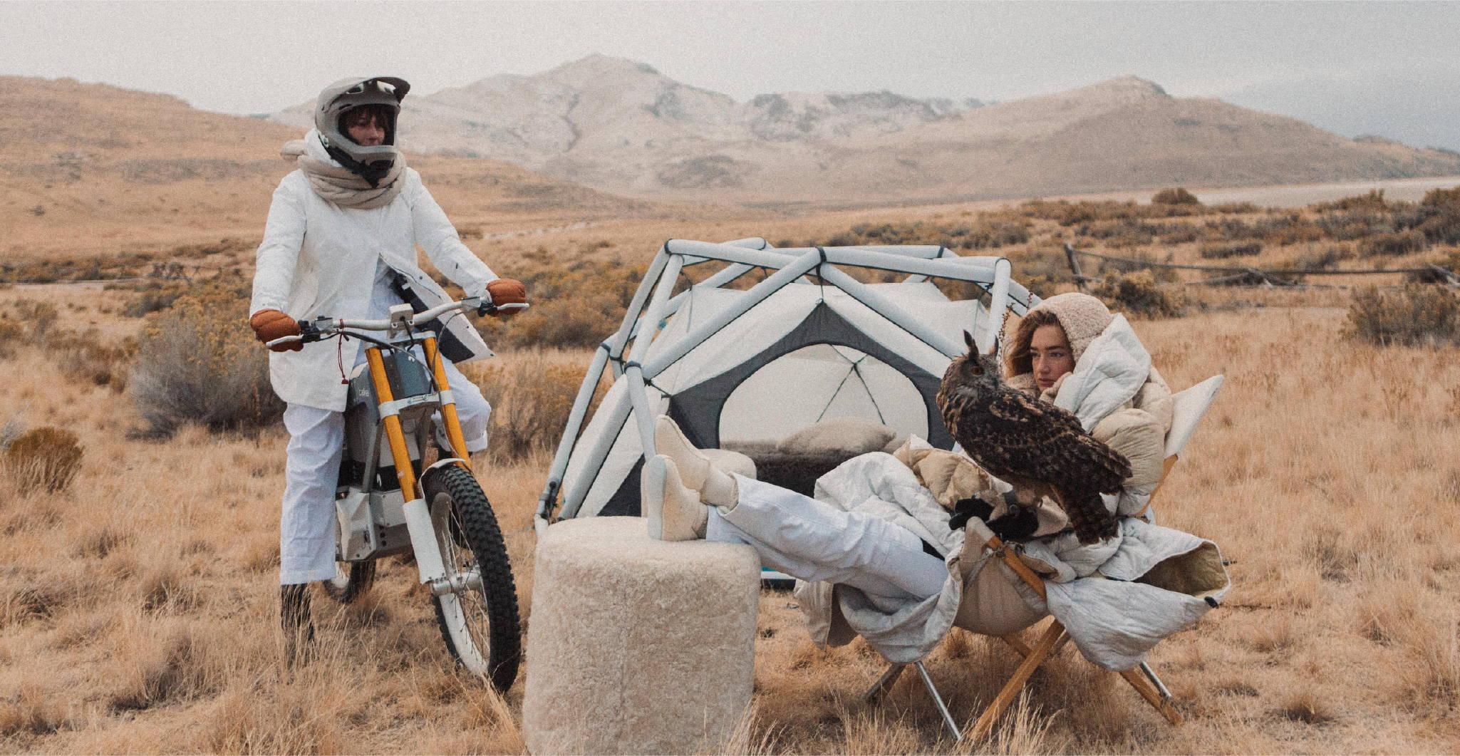 Woman on a dirt bike outside of a tent with an owl in Westerlind Rumpl blanket