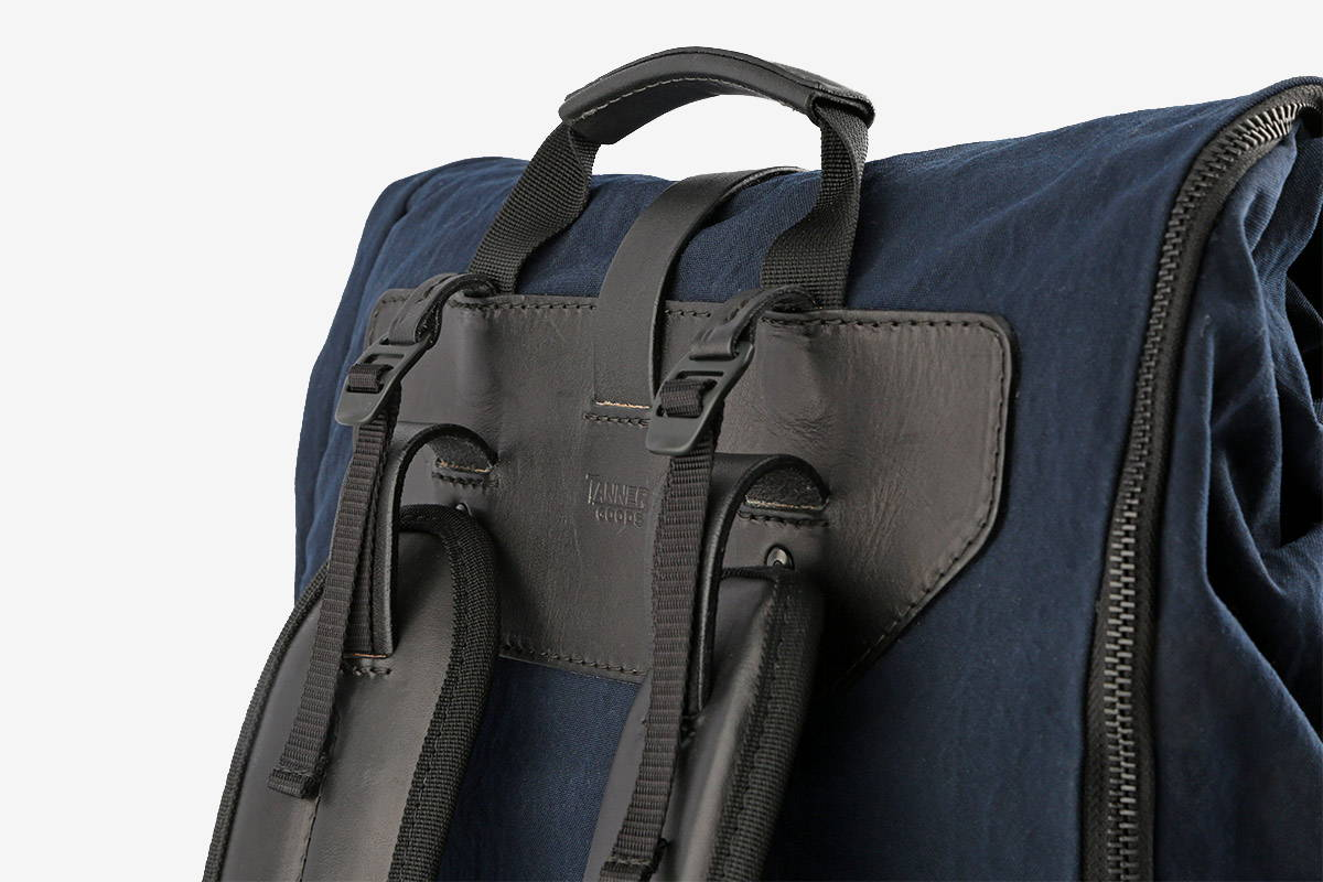 A navy blue backpack with adjustable strapping at the top of the shoulder pads.