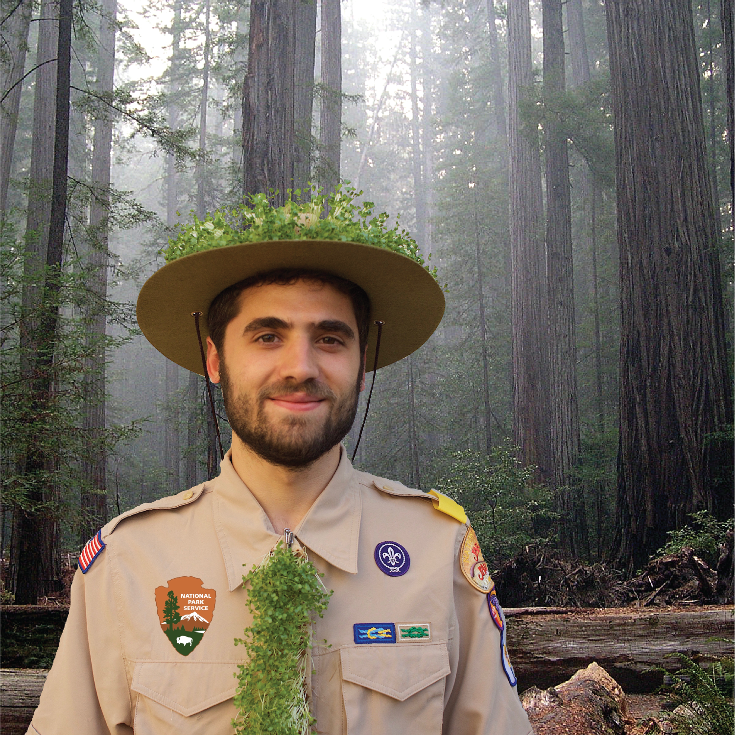 Man dressed as a park ranger with living clothing made of fully grown microgreens.  He has a hat with a living microgreens rim and a microgreens tie.