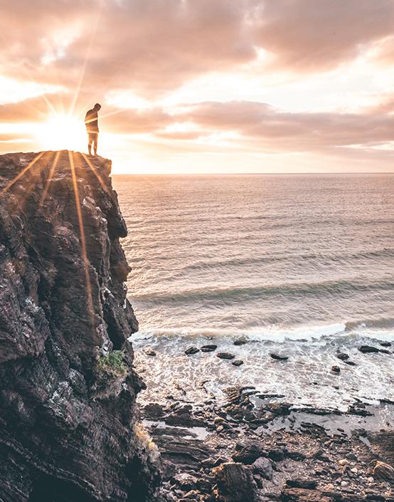 man on oceanside cliff in the sunset