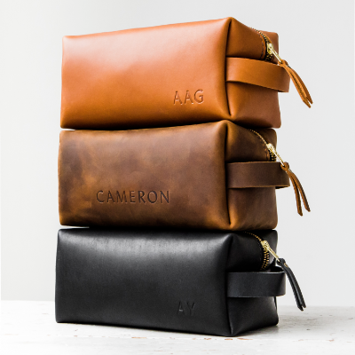 a stack of 3 handmade leather dopp kits by portland leather goods