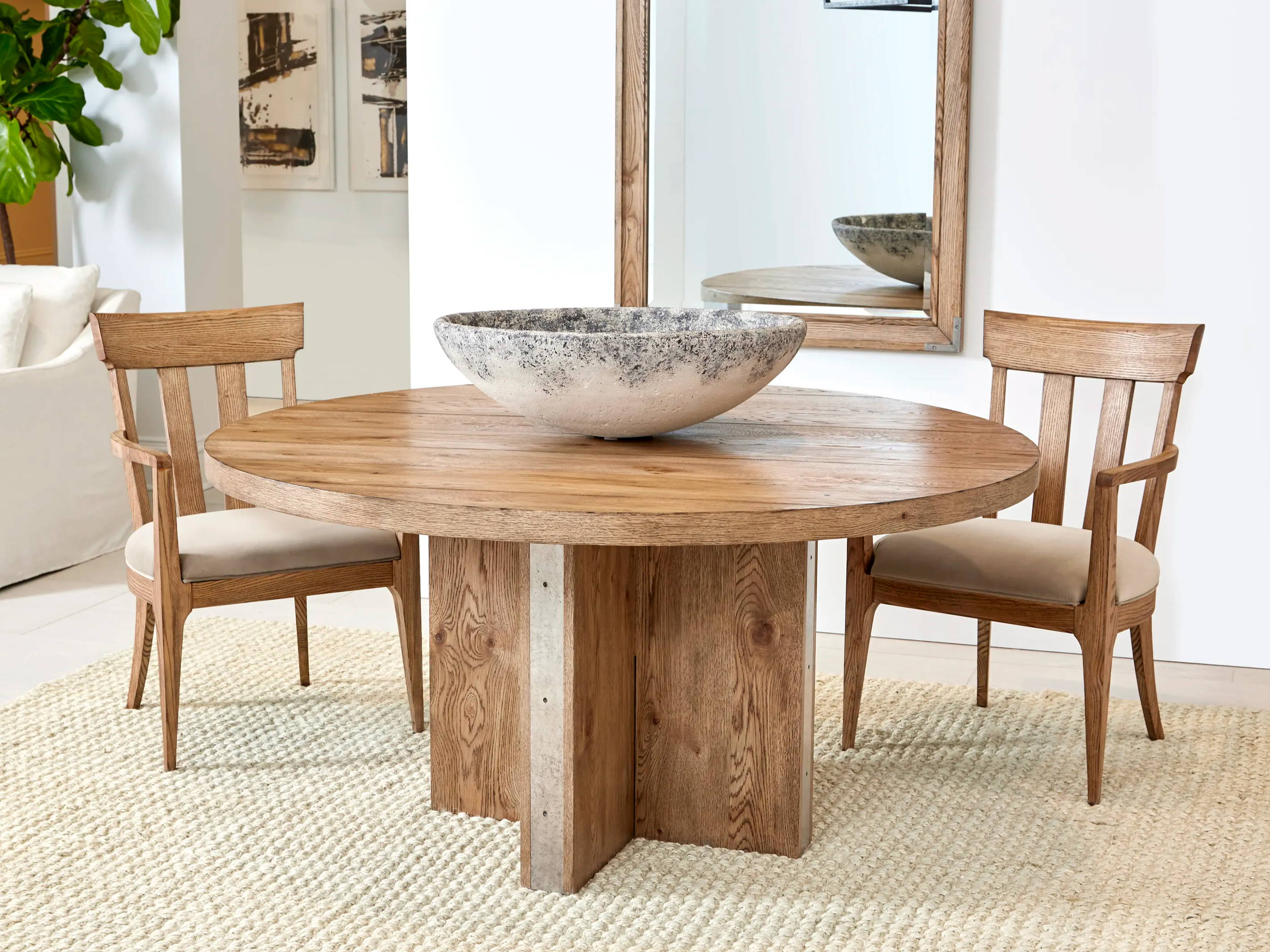 round wood dining table with two wood with fabric seat dining arm chairs