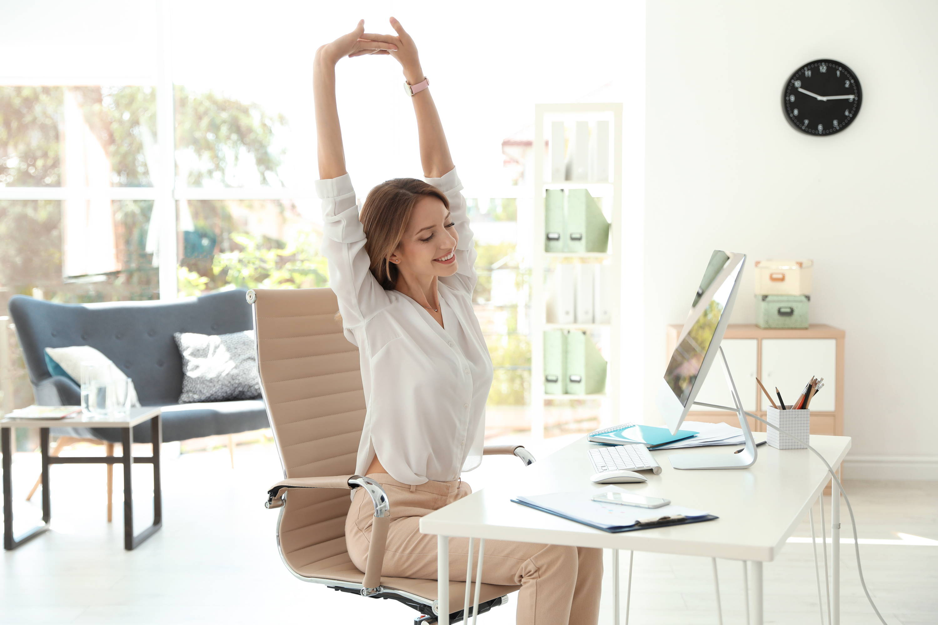 Woman at desk stretching her clasps hands upward .
