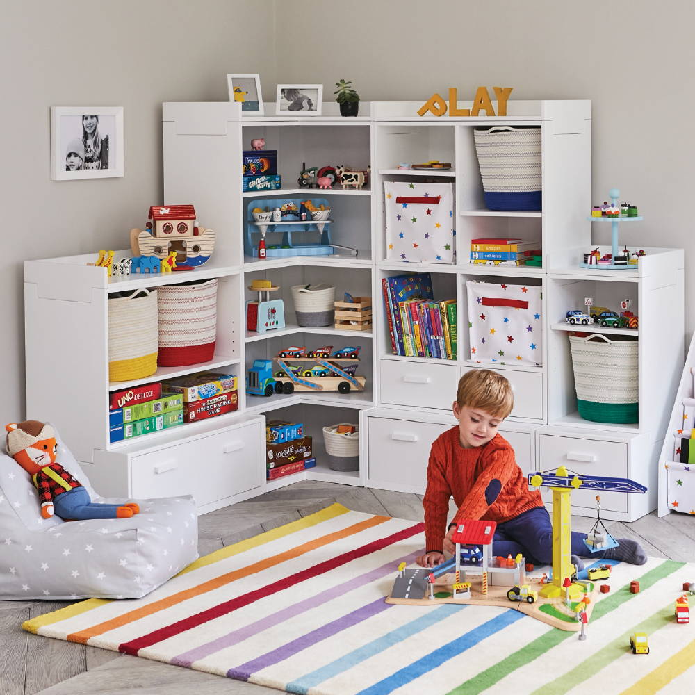 White storage unit filled with kids' toys and rainbow rainbow rug