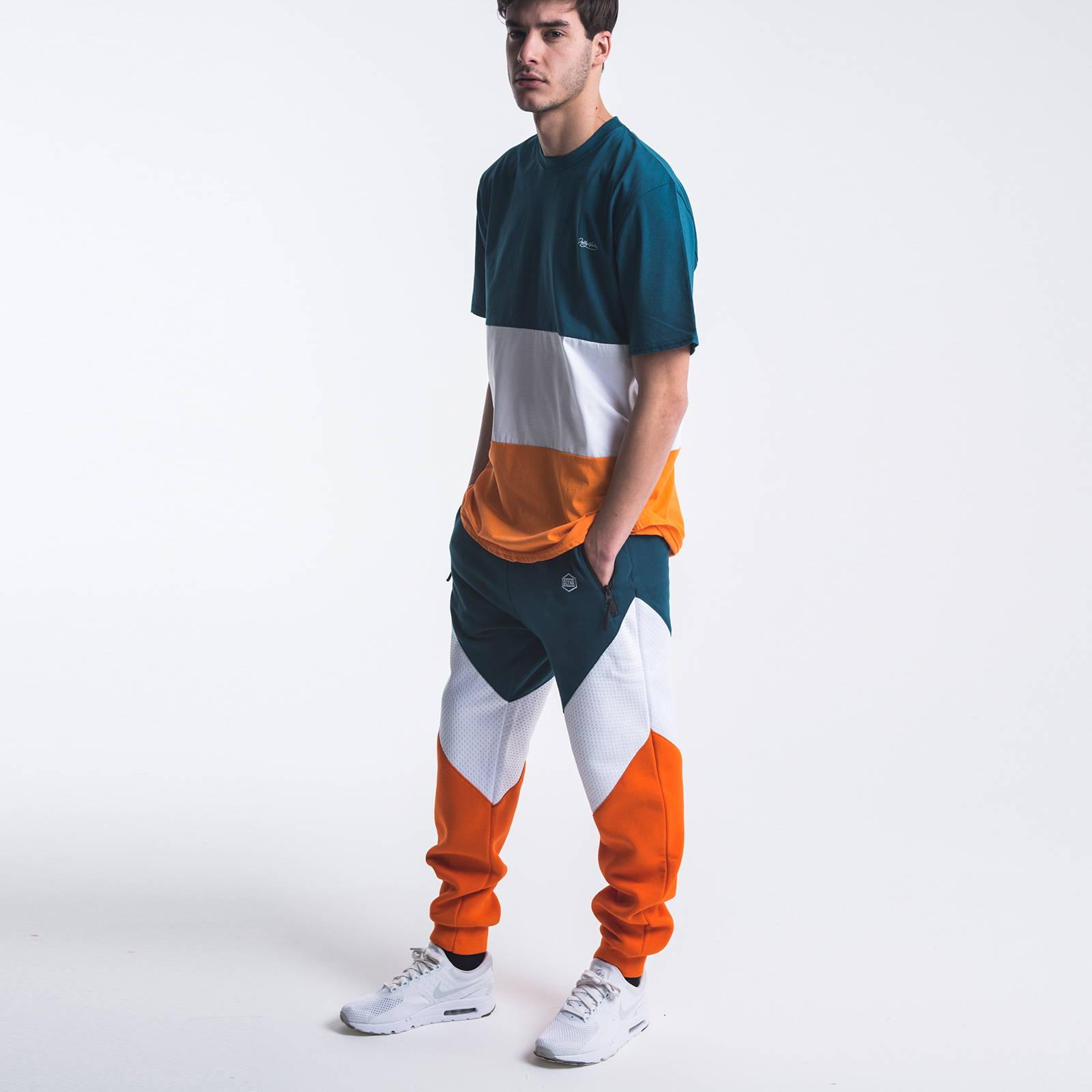 Pantaloni in felpa garzata Dolly Noire. Taglio  Victorious a tre bande: felpa arancio, tessuto bianco forellato, e felpa blu petrolio. Tasche con zip spalmata, e tira zip in silicone. Logo Dolly Noire ricamato vicino alla tasca.