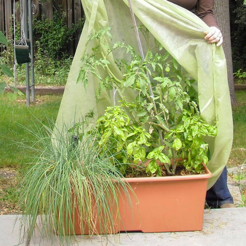 Woman putting a protective cover over her EarthBox original growing system