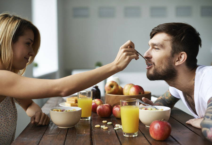 Woman feeding man herb infused food with a spoon