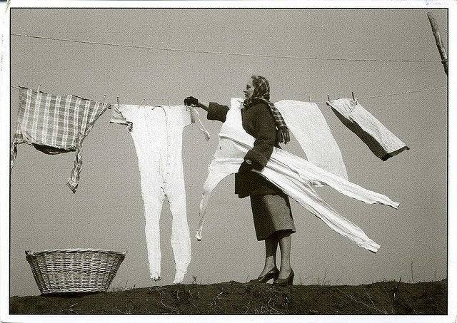 House wife removing frozen long johns from a clothes line, 1950's
