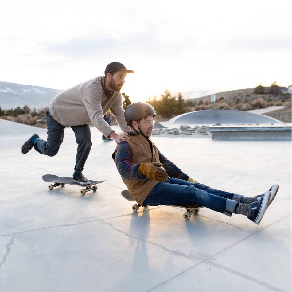 Man pushing friend on skateboard