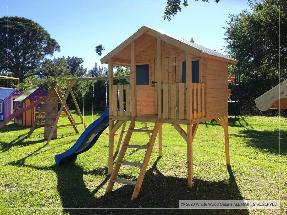 Wooden DIY playhouse on stilts with stairs and a blue slide on grass and blue sky in the background by WholeWoodPlayhouses