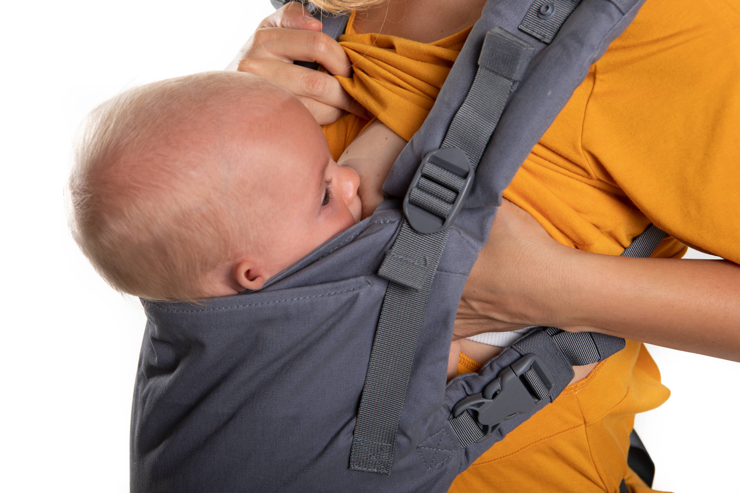 baby breastfeeding in Boba X carrier with mom wearing a mustard colored breastfeeding shirt