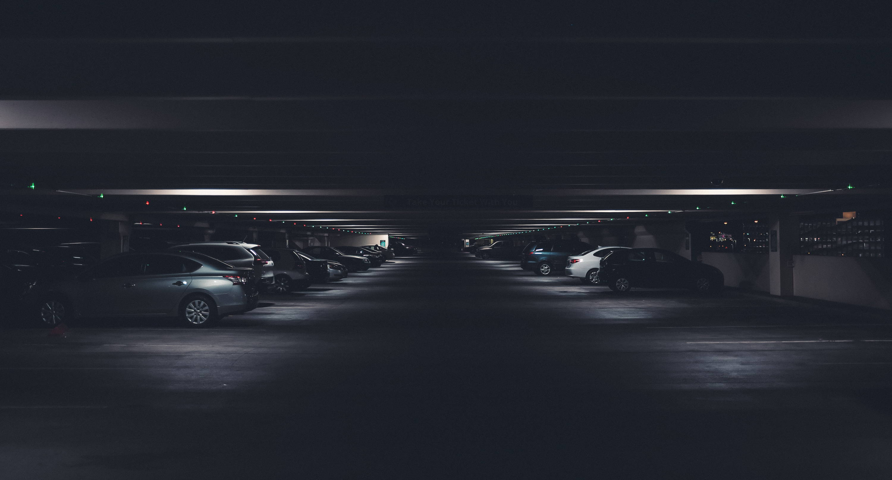 A series of cars parked in a dark underground parking lot.