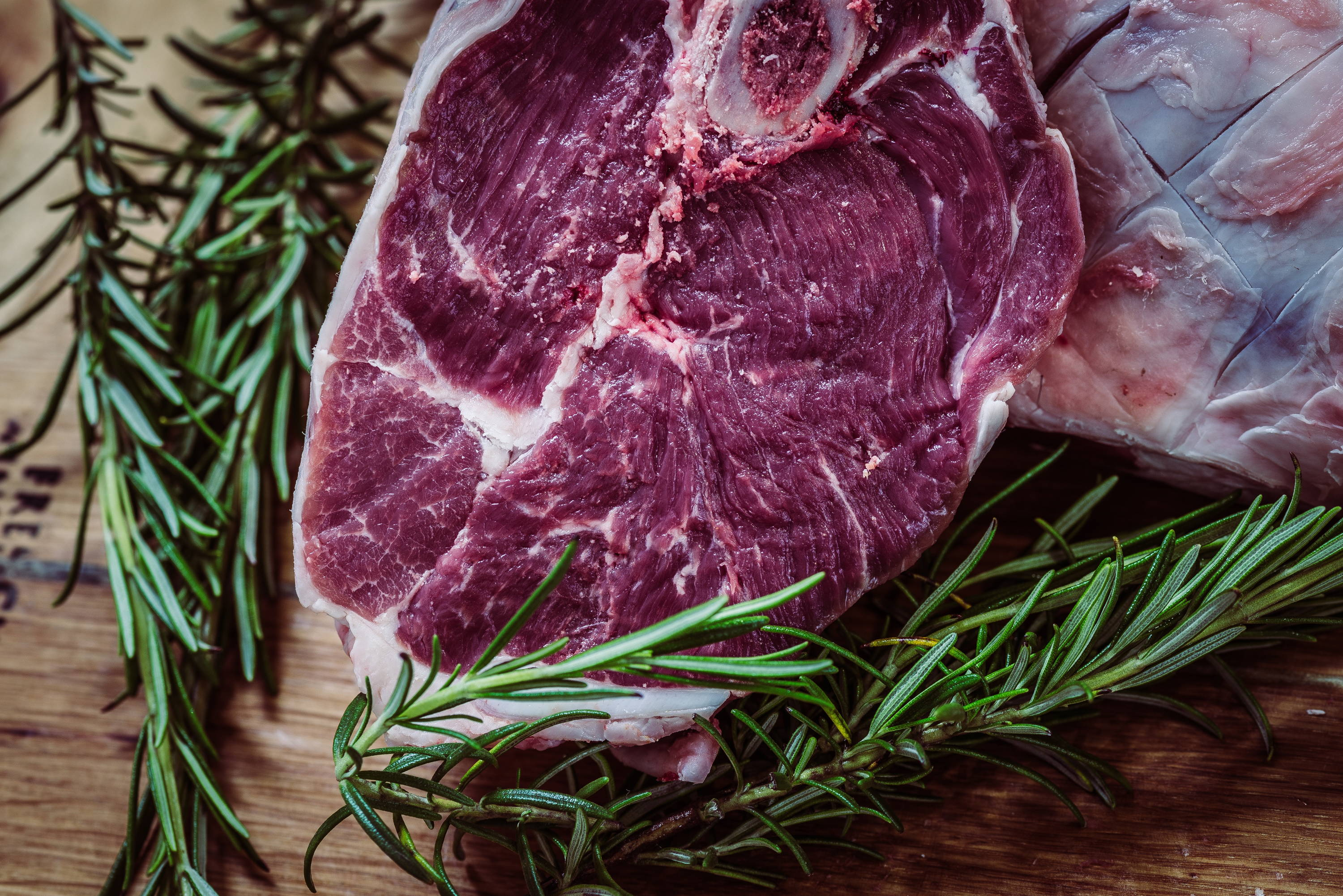 Raw steak with rosemary being prepared.