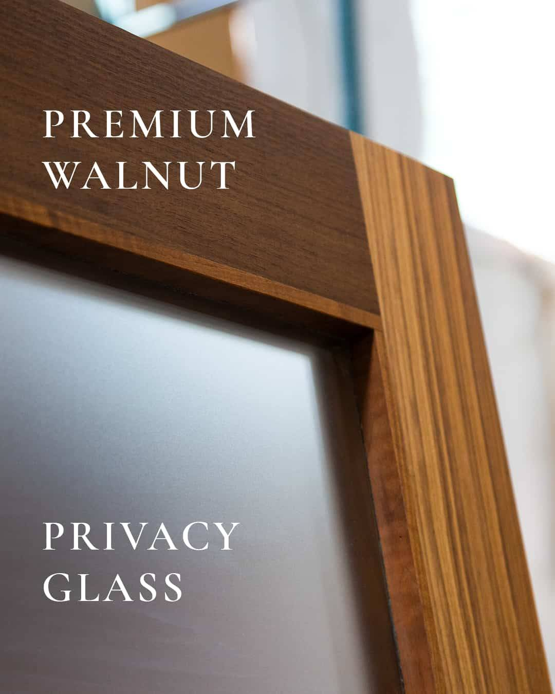 Modern Five Panel Glass Sliding barn door handcrafted with Premium Walnut wood and Crystal etched Glass. Close up shot of left edge showcasing wood grain and glass.
