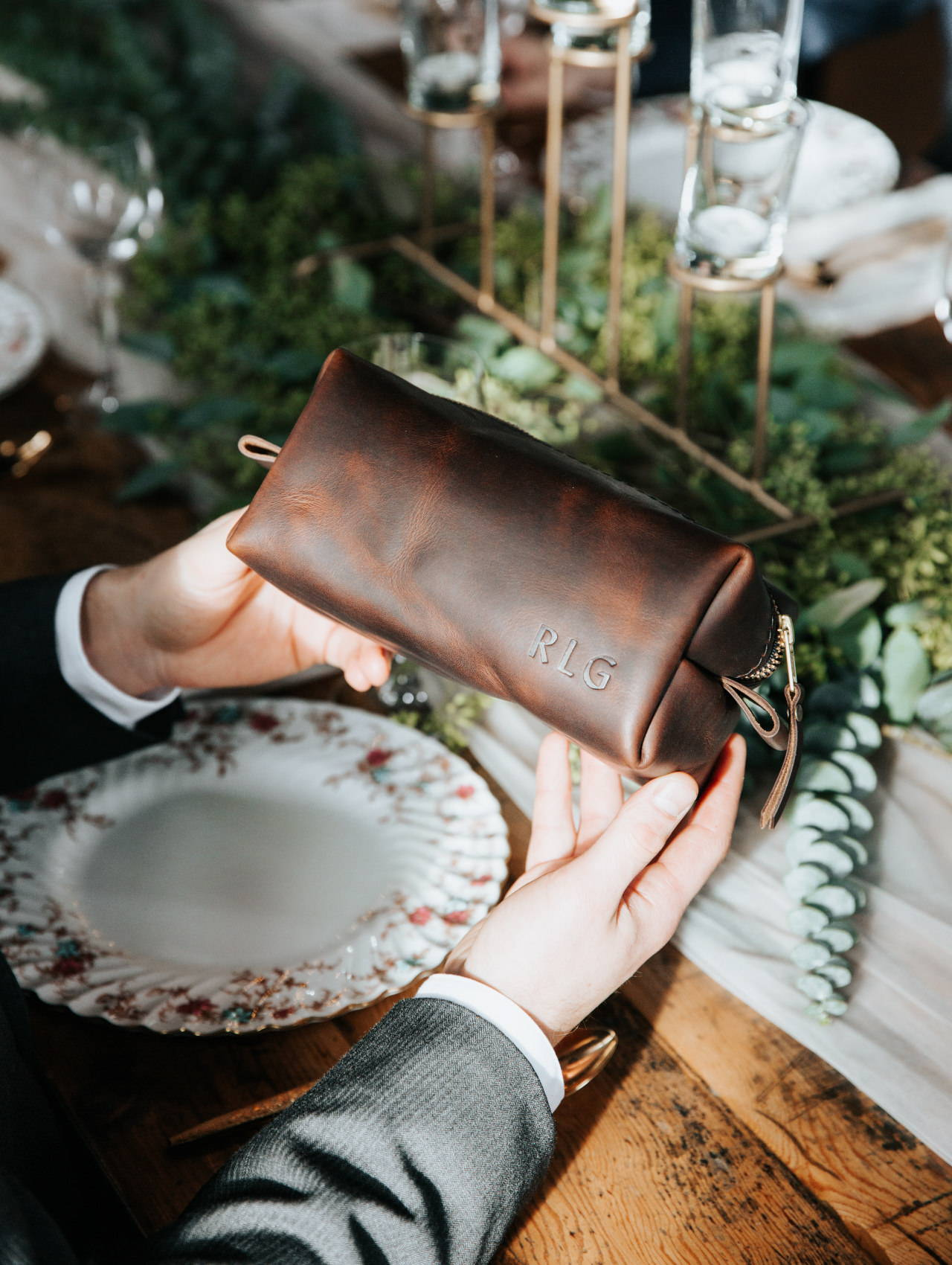 groomsman hands holding a grizzly handmade leather dopp kit by portland leather goods