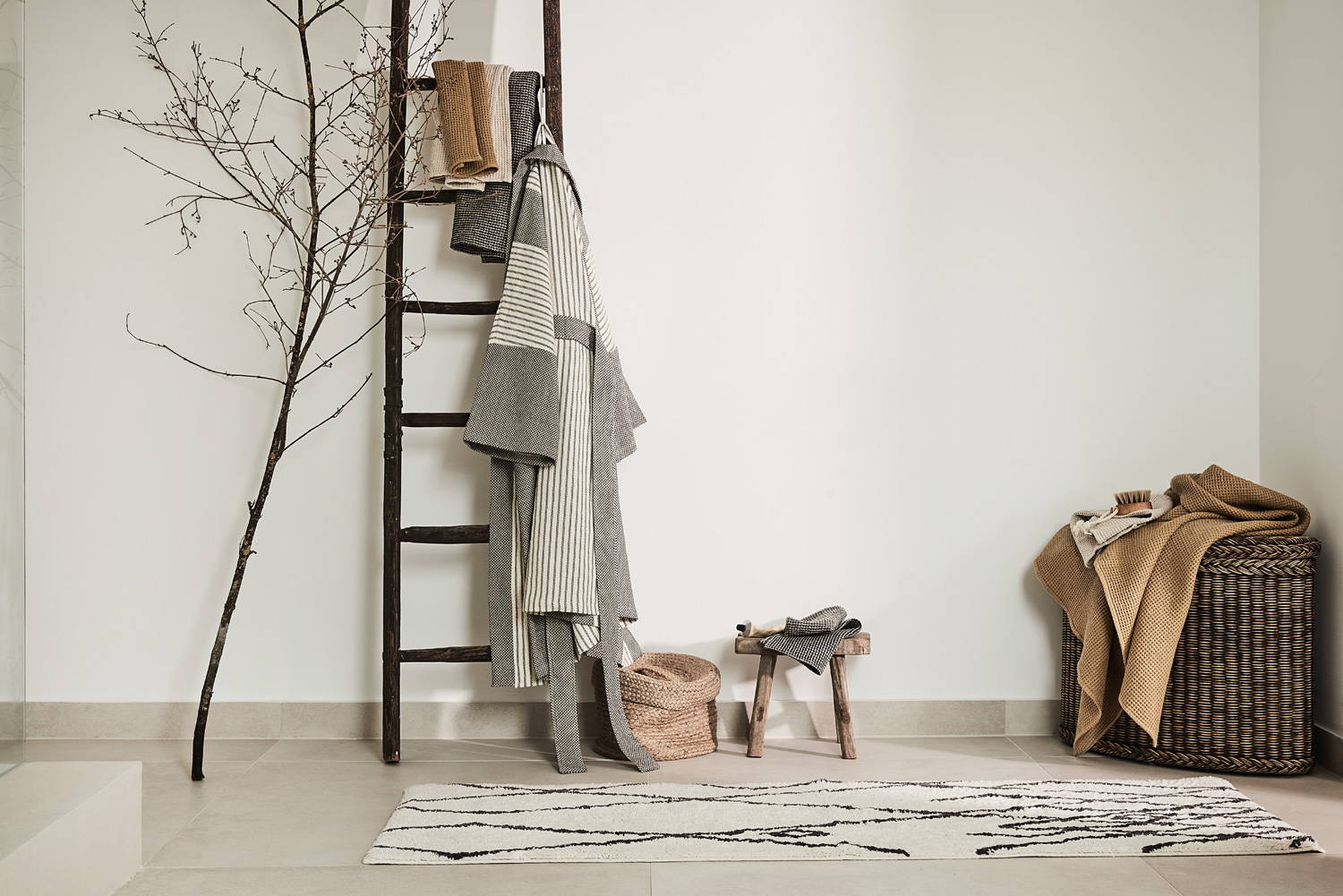 Lagom interior decor with beni rug, ladder, bathrobe, towels and rattan basket