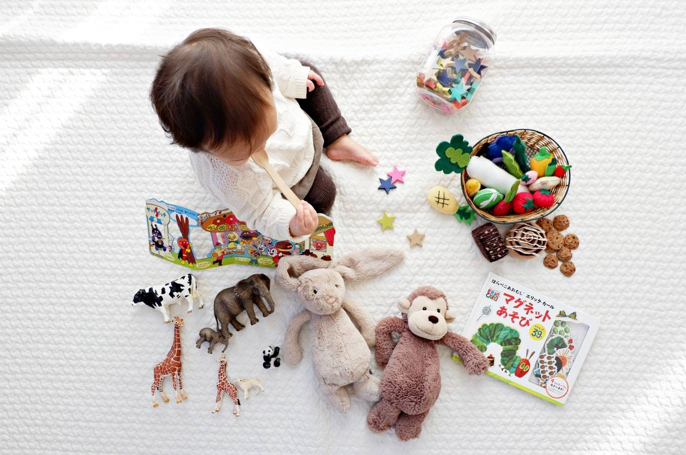 Baby Sitting On White Cloth Surrounded By Toys