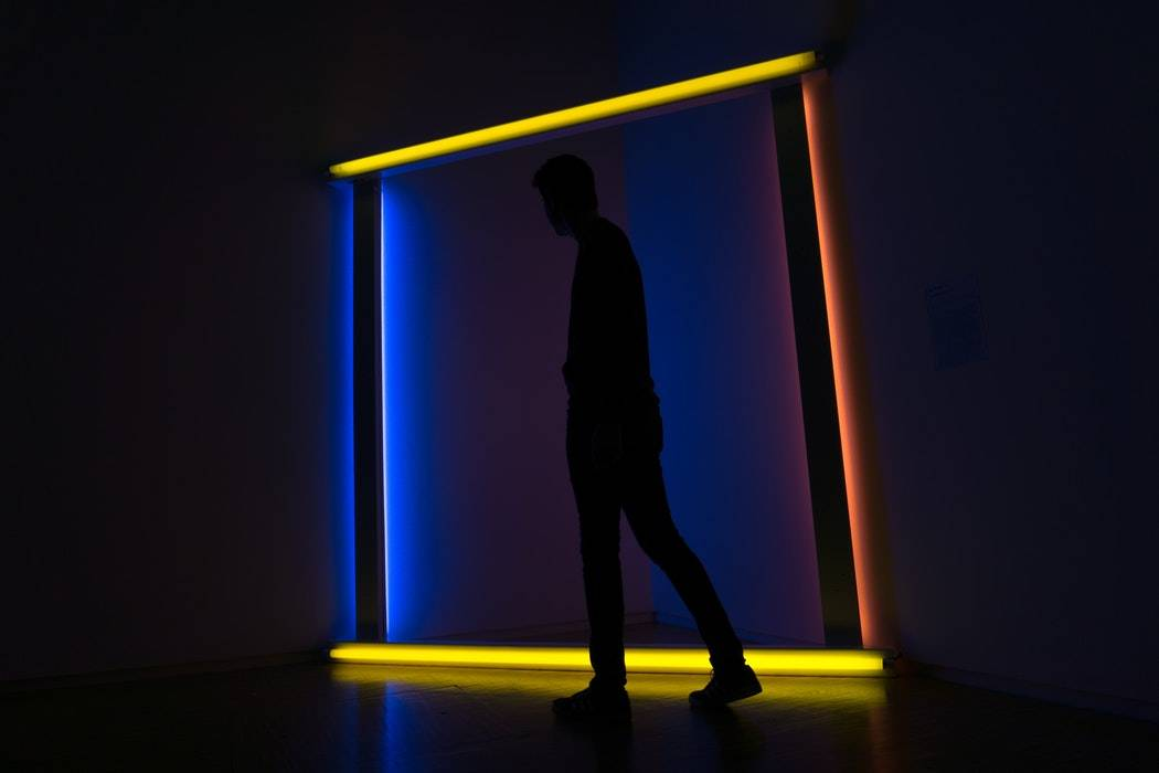 A man walking in front of neon lights in art gallery