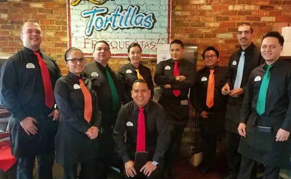Waitstaff wearing all black with a colorful solid color tie