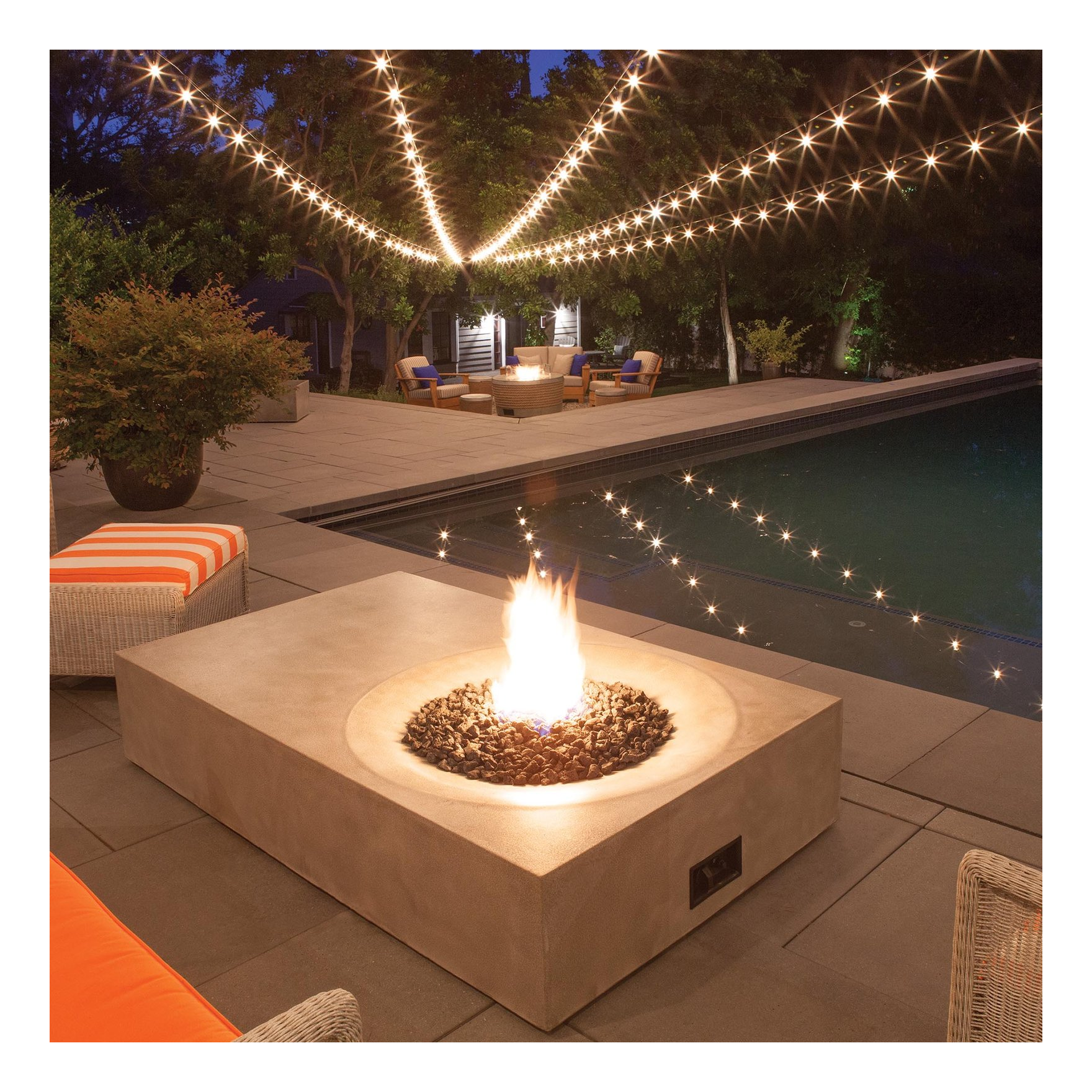 A modern concrete fire pit with stunning lighting by a pool