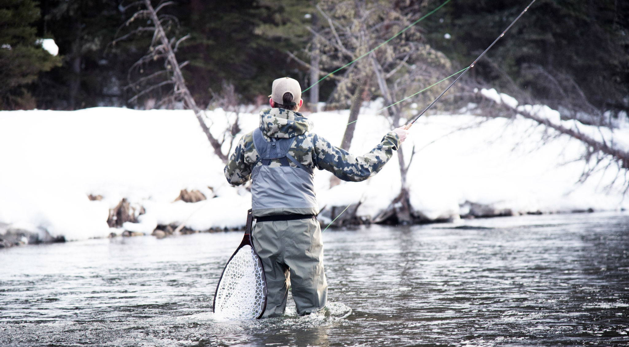 Man fly fishing wearing a JeltX Adjustable belt as a wader belt.